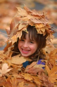 Clean Gutters and Drains Protect Your House and Garden - child playing in leaves